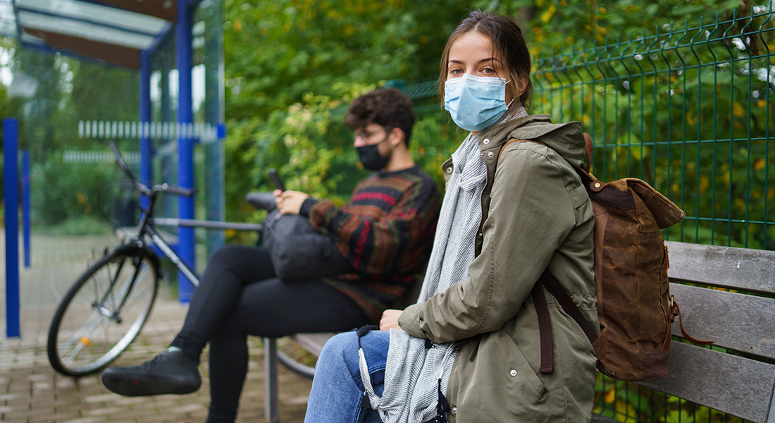 People with masks waiting for a bus